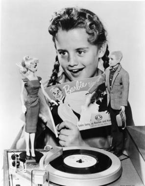 "A little girl gaily singing along with a 7"" record called 'Barbie Sings' Barbie and Ken stand by, on a portable phonograph player."